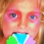 Child With Blue Eyes in Colorful Makeup Eating Lollipop