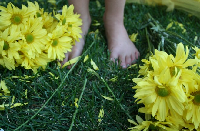 Girl standing in grass with yellow flowers