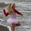 Cute Little Girl in Pink Dances on  Beach during the Kite Festival.
