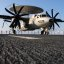An E-2C Hawkeye sits on the flight deck of the aircraft carrier USS Abraham Lincoln while Sailors man the rails