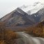 The Denali road leading toward snow covered mountains