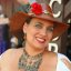 Portrait of a lovely lass with a red flower in her hat
