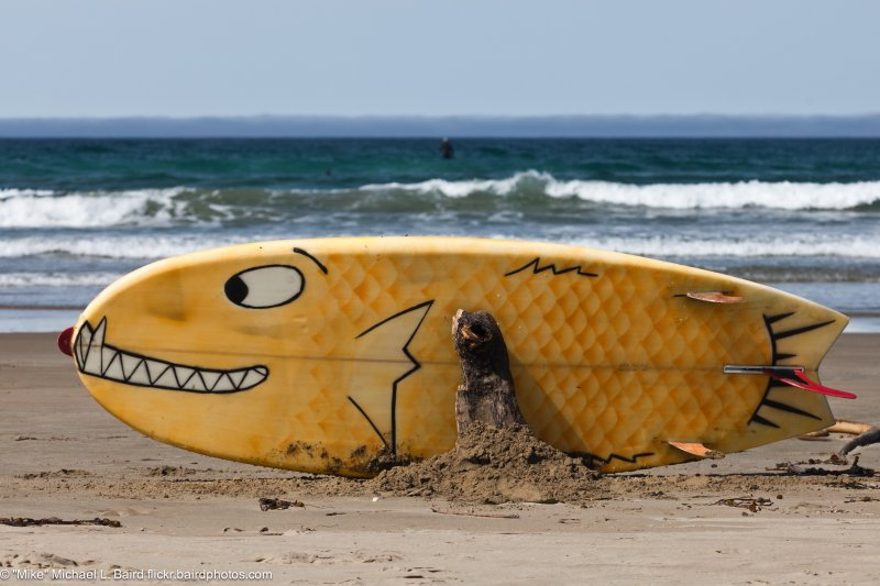 A surf board with bottom art - a creative artistic smiling fish pattern painted on the bottom