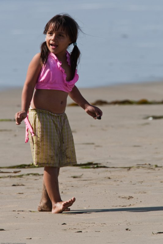Cute Little Girl in Pink Walking Beach.  People scenes, on the beach on Morro Strand State Park just north of Morro Rock in Morro Bay, CA.  23 August 2009