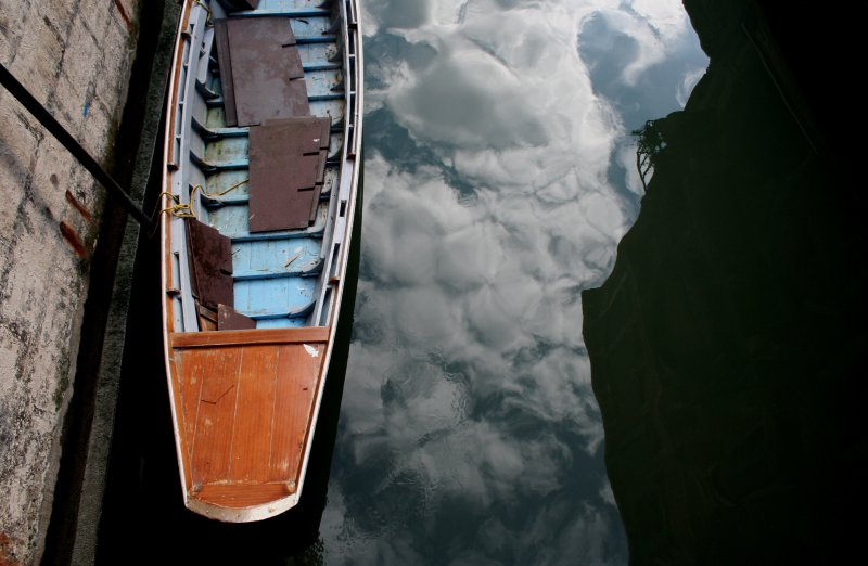 reflected clouds and a boat