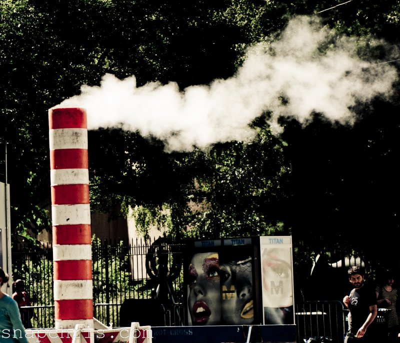 Girl from Ad sign checks out smoke stack