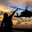 Aviation Electrician's Mate Airman John Broughton signals to an HH-60H Seahawk helicopter as it takes-off.