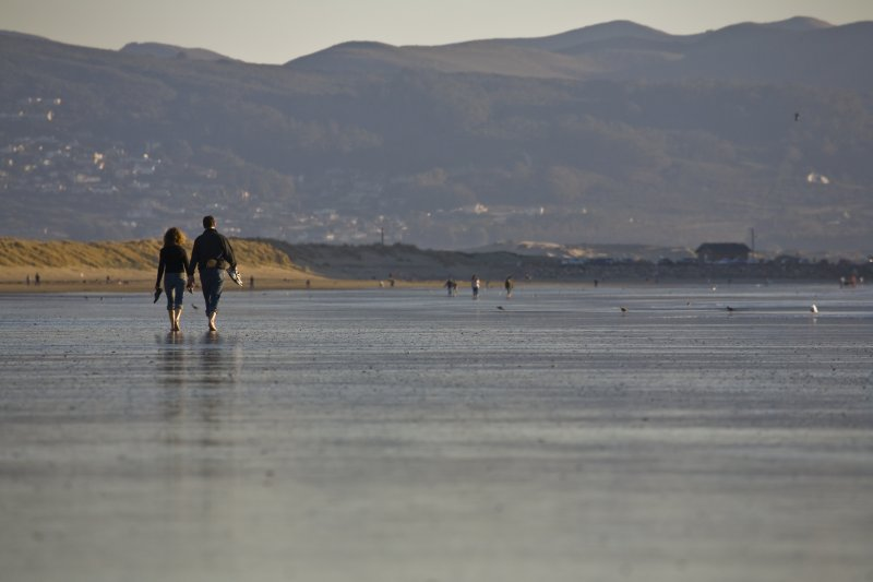 A couple (two people) walking the Morro Strand State Beach, Morr