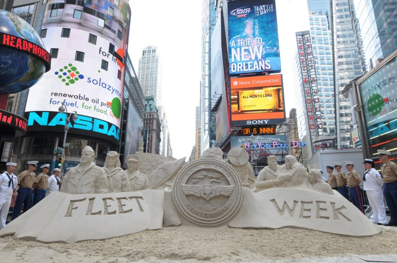 """Service members surround a sand sculpture created for a special taping of the """"Sand Masters"""" television show"""