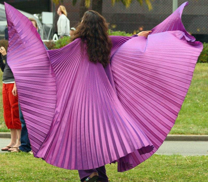 Nikki Nez twirling in purple at a God is Love gathering in SF's Golden Gate Park